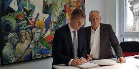 Kai Rosenberger und Martin Kunzmann unterzeichnen einen Brief