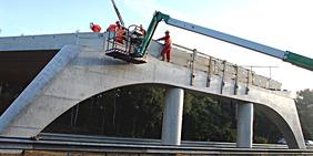 Bauarbeiter arbeiten mit Kran an Autobahnbrücke