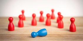 Eine umgefallene blaue Spielfigur, umringt von mehreren roten, stehende Spielsteinen