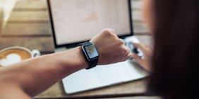 Frau am Schreibtisch mit Laptop schaut auf die Armbanduhr