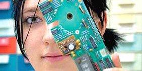 Eine Jugendliche hält eine Speicherplatine vor ihr Gesicht.
