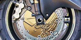 Großaufnahme der Scheibenbremse eines Motorrads: Die Bremsscheibe besteht aus einer überdimensionalen 2 Euro-Münze