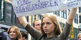 """Eine Studentin trägt ein Banner """"Keine Studiengebühren"""""""