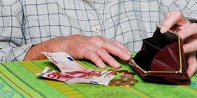 Hände einer älteren Frau zählen Geld aus Geldbörse