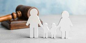 Familie als Silhouette vor einem Richterhammer