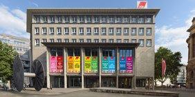 Willi-Bleicher-Haus mit Regenbogenbannern vom Gustav-Heinemann-Platz aus gesehen