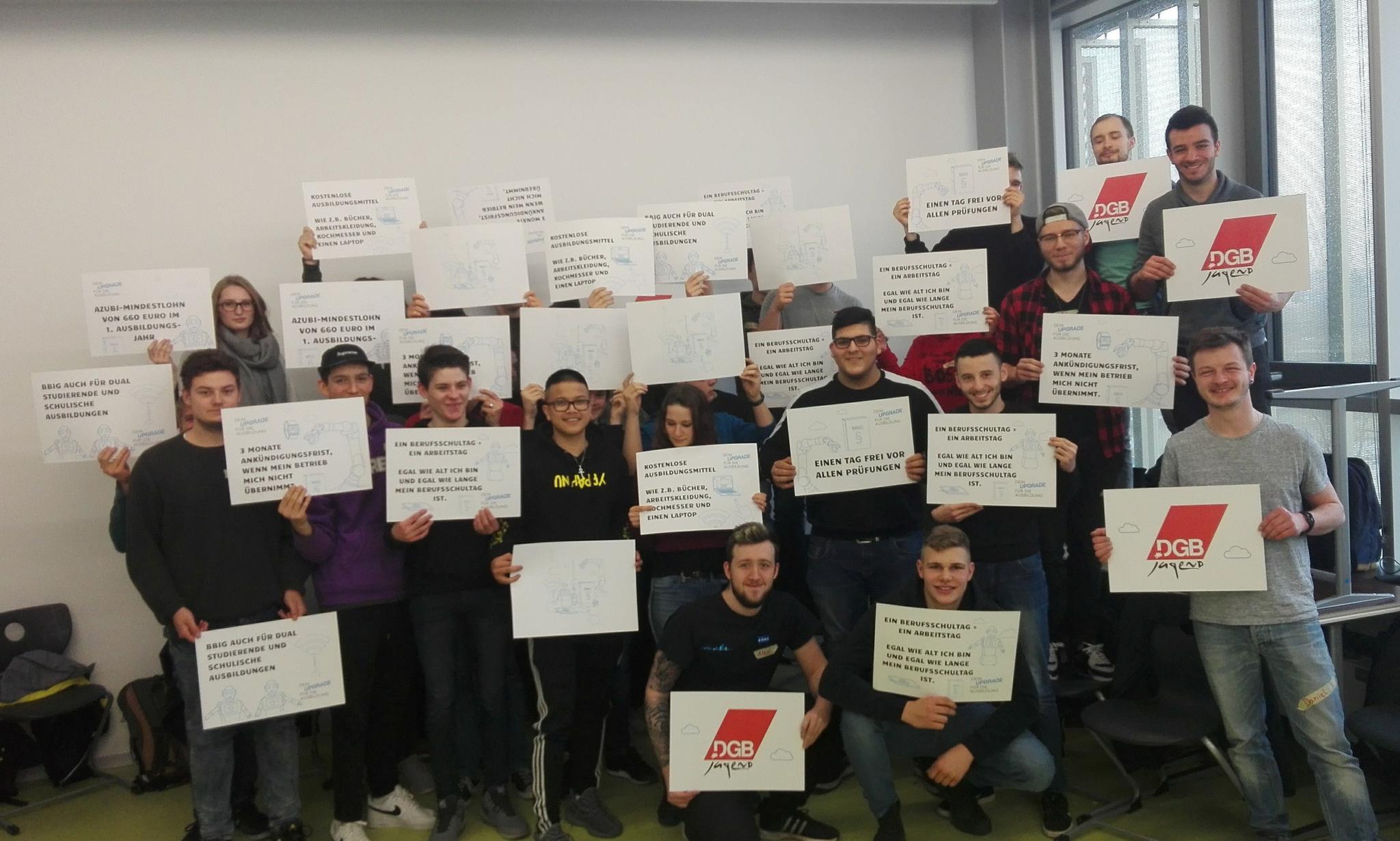 Auszubildende aus Karlsruhe, die eine Ausbildung zum_r  Mechatroniker_in und zum_r Elektroniker_in durchlaufen, halten Plakate hoch.