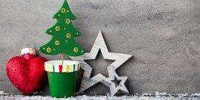 Bunte Weihnachtsdekoration vor einer grauen Holzwand